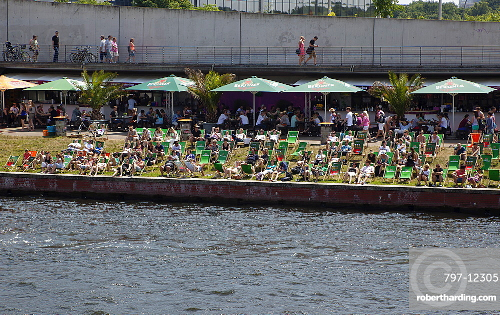 Germany, Berlin, Mitte, people sunbathing on the banks fo the river Spree.