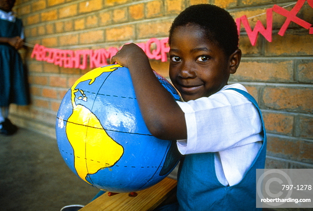 MALAWI  Blantyre Schoolgirl with papier mache globe teaching aid made by PAMET who recycle everything from newspapers to elephant dung