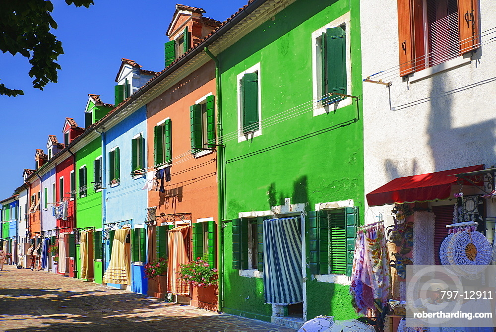 Italy, Veneto, Burano Island, Colourful row of house facades with outdoor display of lace for sale.