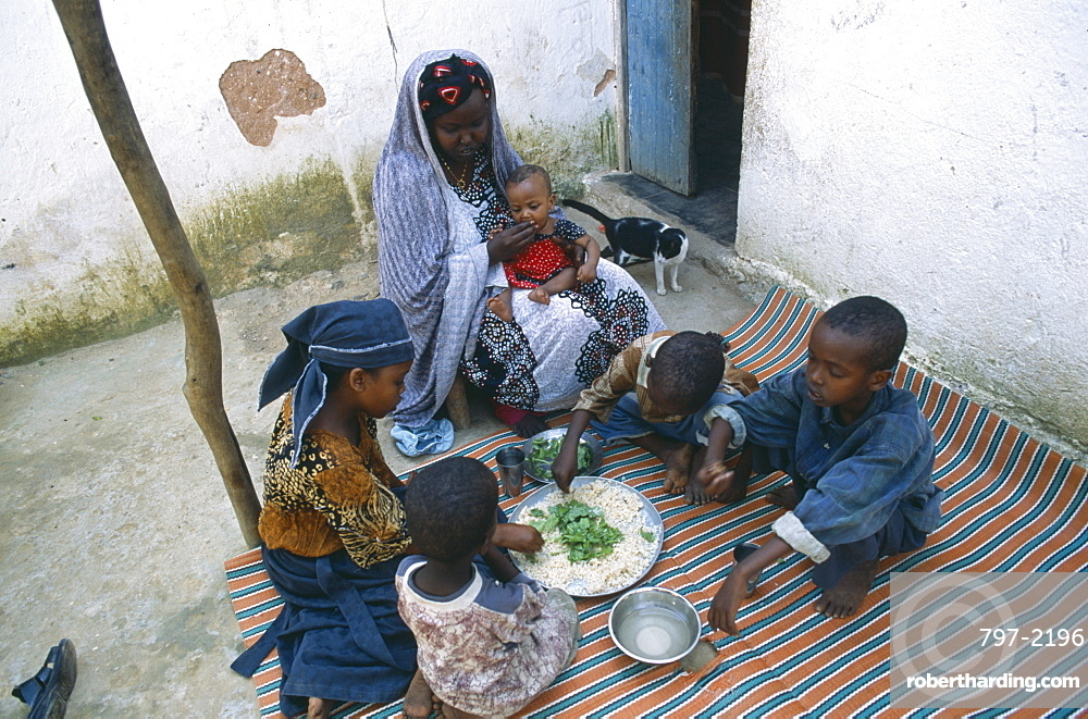 SOMALIA  Baidoa Woman and children eating lunch from communal dish using the right hand.  At a family meal men are usually served first and women and children eat seperately later.