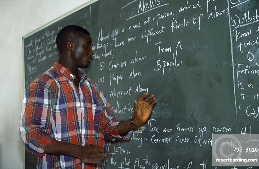 NIGERIA  Kano English teacher standing beside blackboard giving grammar lesson. African Learning Lessons Nigerian Teaching Western Africa