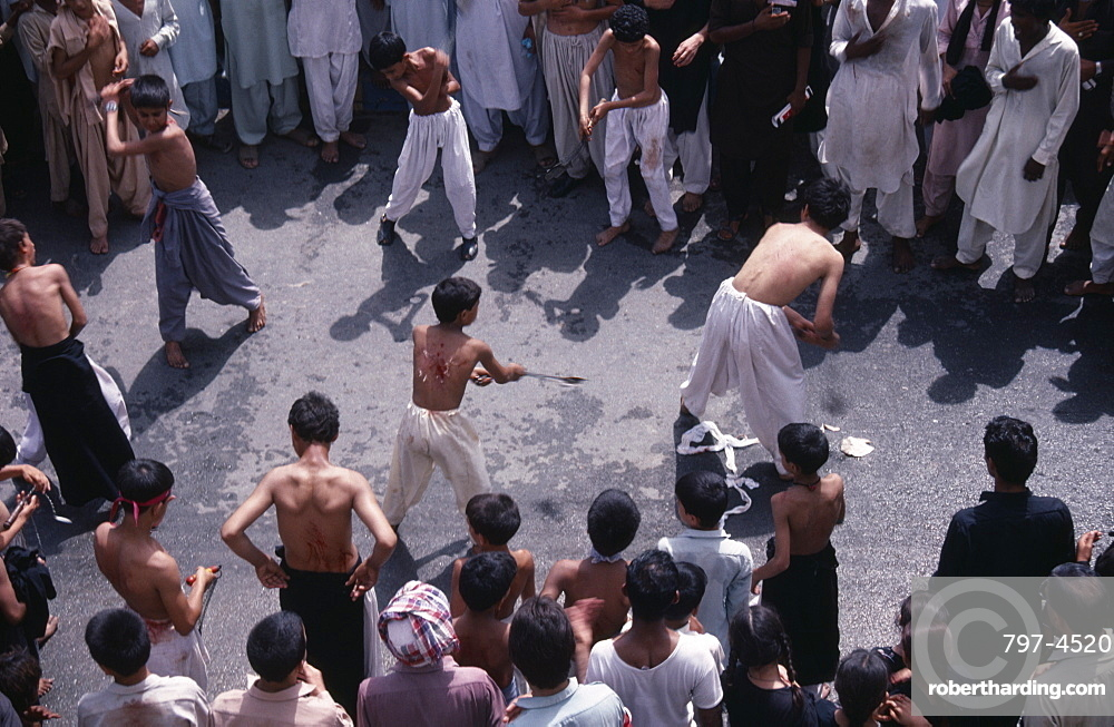 Mohurrum Shia muslim festival commemorating death of Husayn ibn Ali grandson of Muhammad, Boys beating themselves with chains in ceremonial mourning, Peshawar, Pakistan