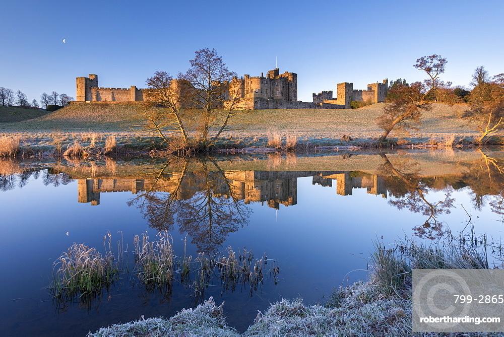 Early morning sunshine in winter illuminates Alnwick Castle in Northumberland, England, United Kingdom, Europe