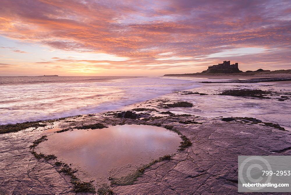 Heart shaped rockpool reflecting the colours of a beautiful pink sunrise, Bamburgh Castle, Northumberland, England, United Kingdom, Europe