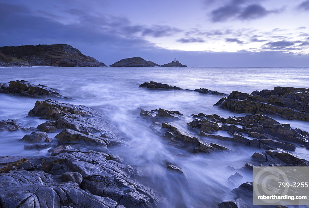 Rocky shore of Bracelet Bay, looking across to Mumbles lighthouse, Mumbles, Wales, United Kingdom, Europe