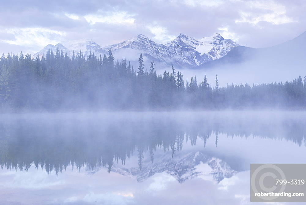 Snow capped mountains reflect in a misty Herbert Lake, Banff National Park, UNESCO World Heritage Site, Canadian Rockies, Alberta, Canada, North America