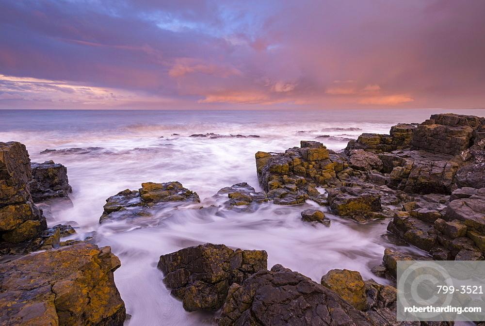 Waves crashing against rocks at sunrise in winter, Porthcawl, Glamorgan, Wales, United Kingdom, Europe