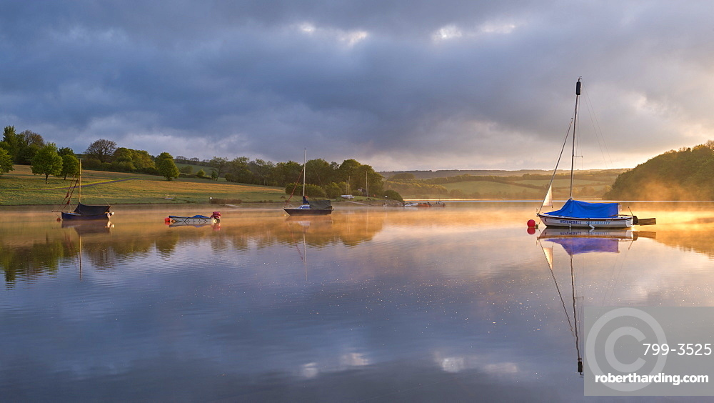 Boats on a reflective Wimbleball Reservoir at sunrise, Exmoor National Park, Somerset, England, United Kingdom, Europe