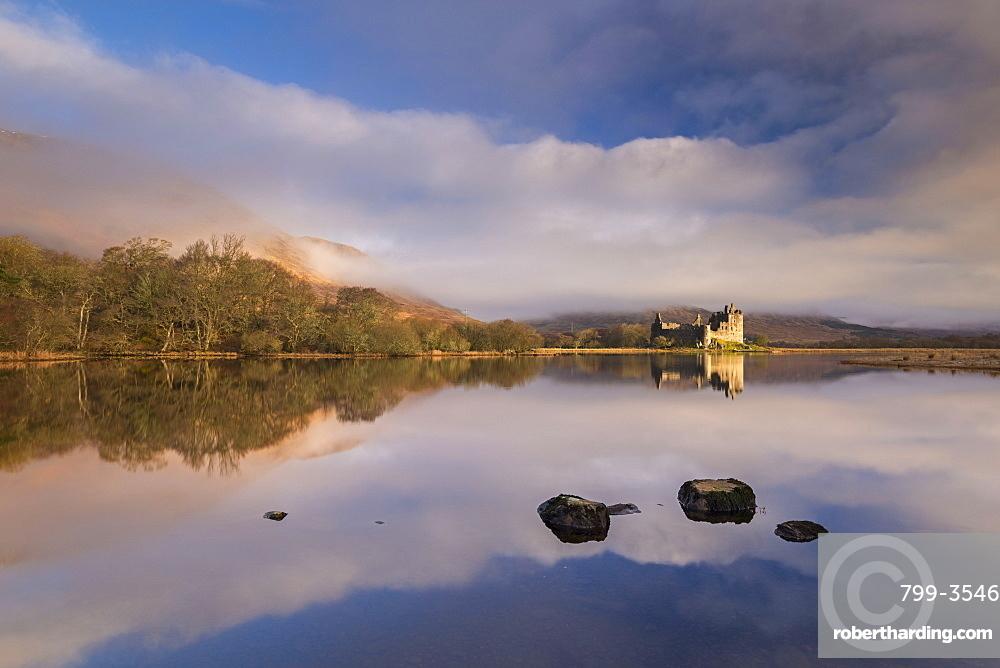 Rich morning sunlight illuminates Kilchurn Castle on a reflective Loch Awe, Argyll, Highlands, Scotland, United Kingdom, Europe