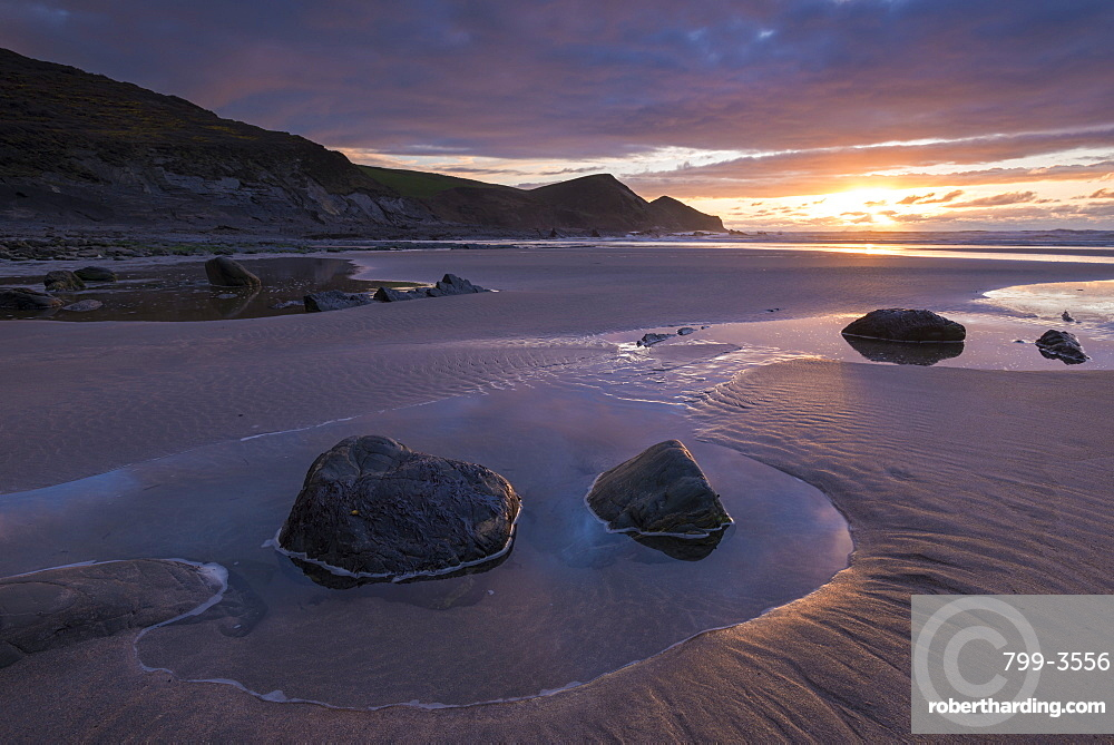 Sunset over a deserted sandy beach in winter at Crackington Haven in North Cornwall, England, United Kingdom, Europe