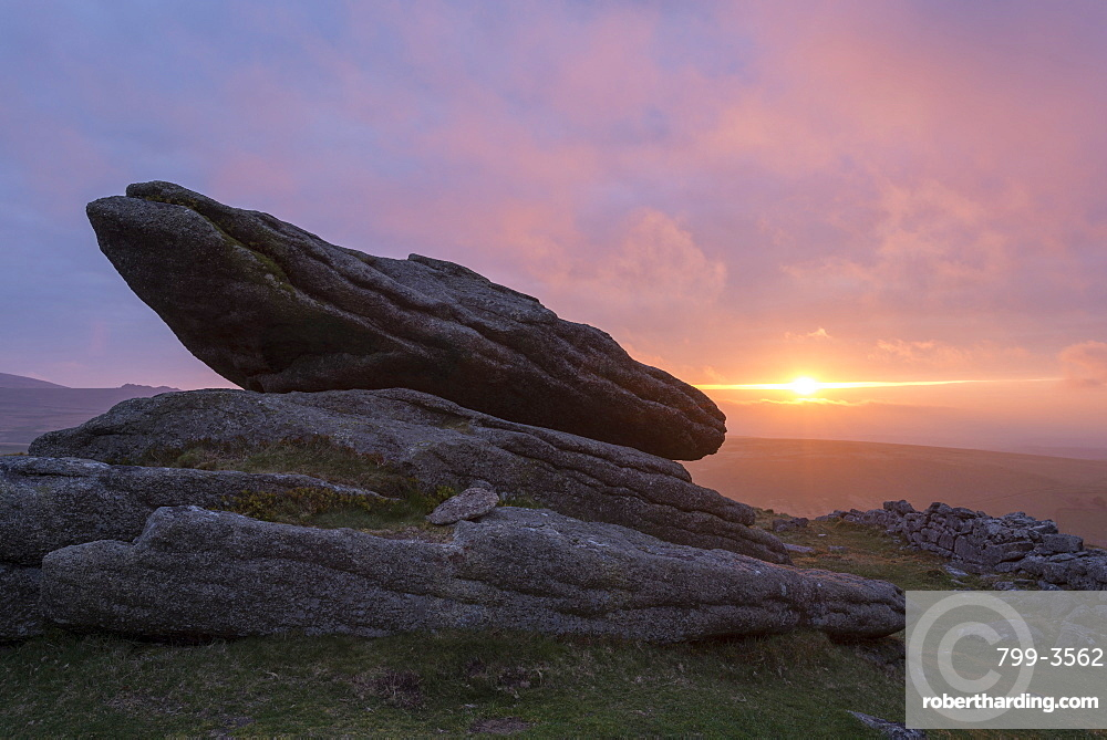 Colourful sunset over a granite logan stone on Belstone Tor, Dartmoor, Devon, England, United Kingdom, Europe