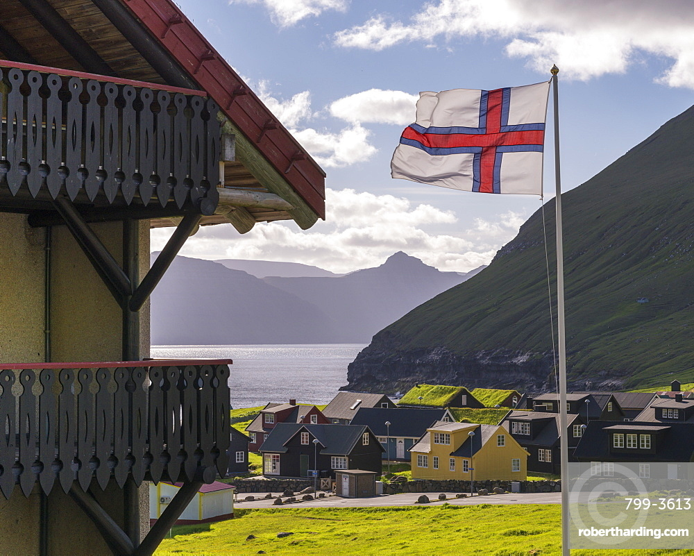 Faroese flag flying in the breeze above the village of Gjogv in the Faroe Islands, Denmark, Europe