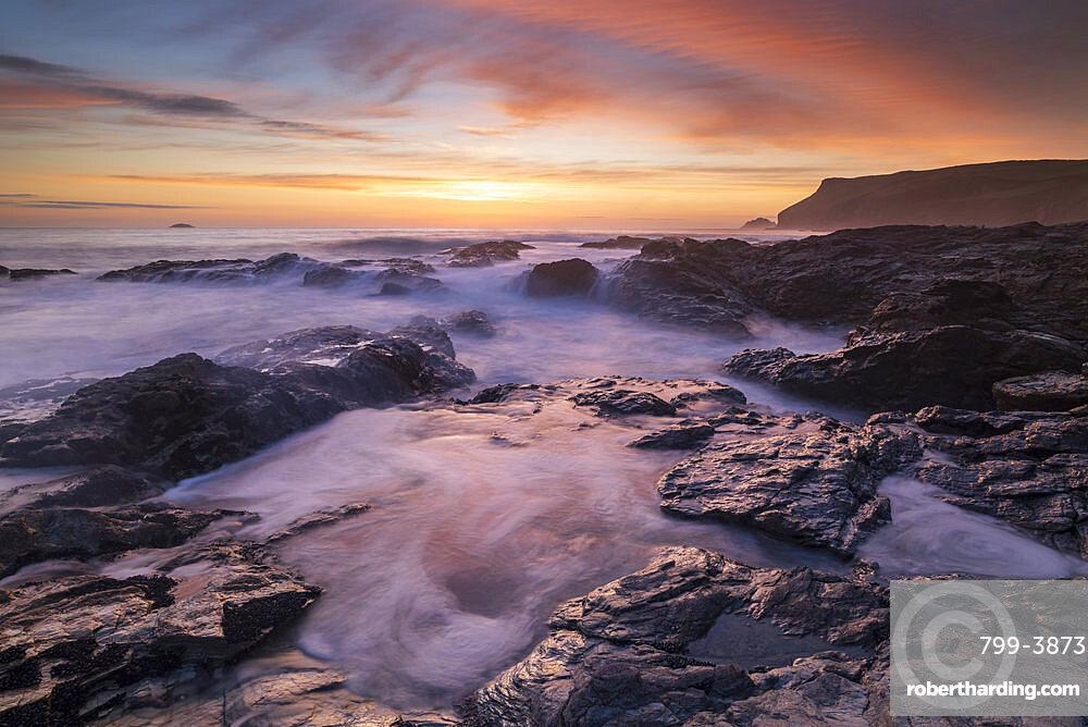 Colourful Cornish sunset above rocky ledges near Polzeath, Cornwall, England, United Kingdom, Europe