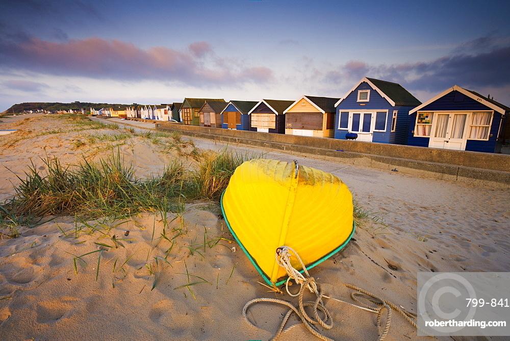 Beach huts and upturned boat at Hengistbury Head, Mudeford, Dorset, England, United Kingdom, Europe