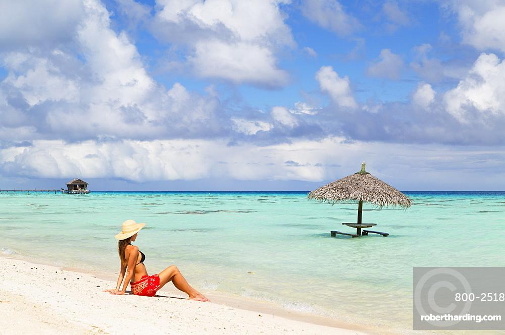 Woman sitting on beach, Fakarava, Tuamotu Islands, French Polynesia, South Pacific, Pacific