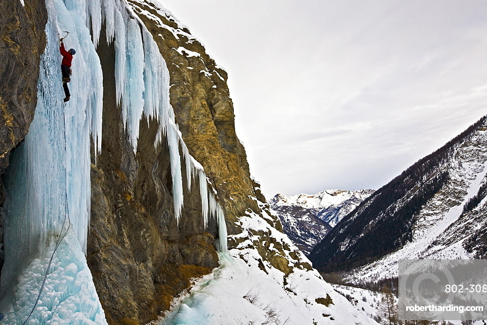 An ice climber ascending a frozen cascade in the Fournel Valley, Ecrins Massif, France, Europe