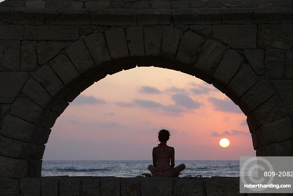 Girl watching sunset in Cesarea, Israel, Middle East