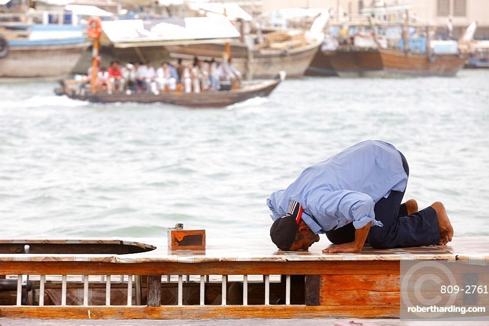 Praying muslim in Dubai harbour, Dubai, United Arab Emirates, Middle East