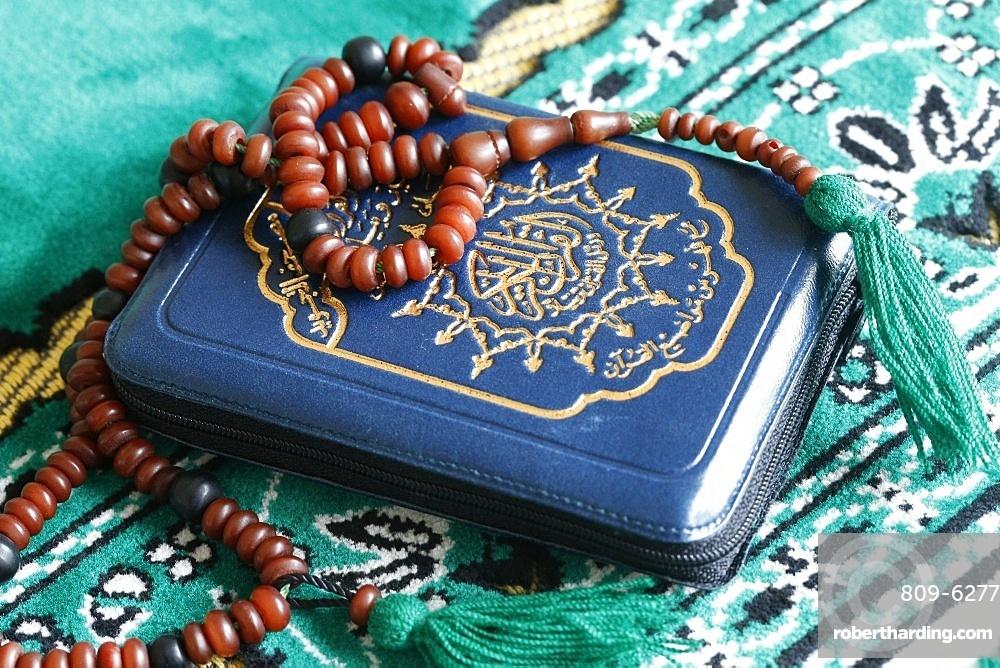 Quran and Islamic prayer beads on a prayer mat, Paris, France, Europe