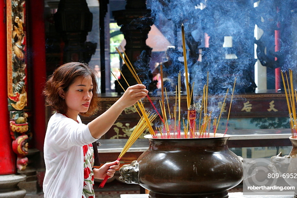 Buddhist worshipper placing incense sticks on joss stick pot, Taoist temple, Phuoc An Hoi Quan Pagoda, Ho Chi Minh City, Vietnam, Indochina, Southeast Asia, Asia