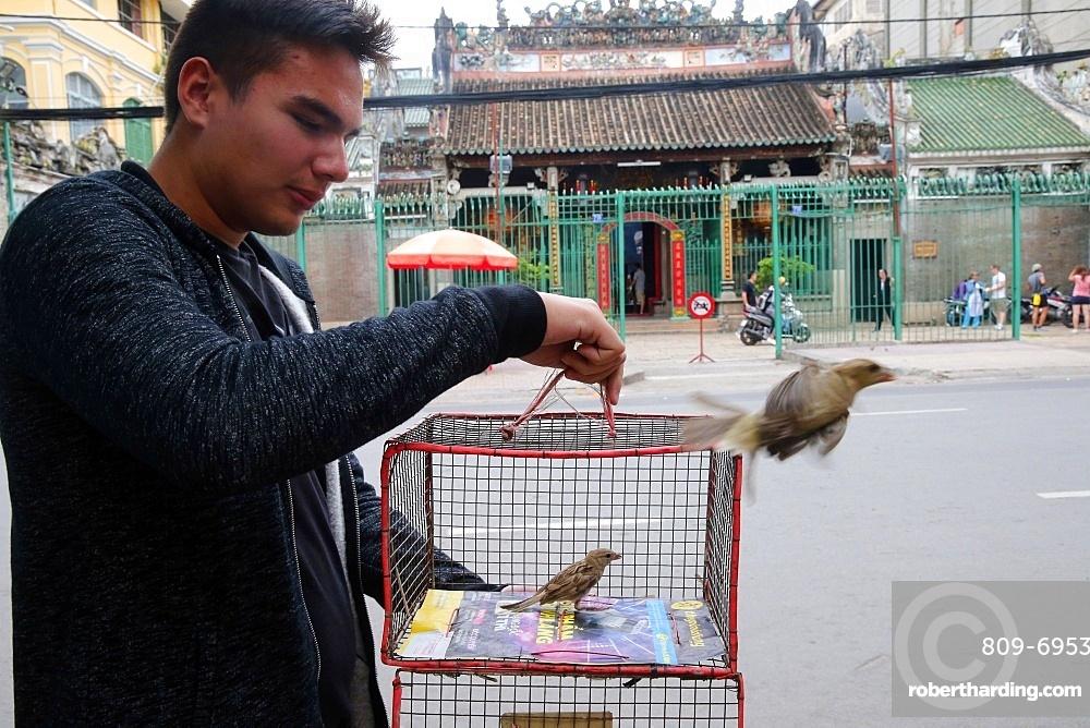 Man releases sparrow, Taoist temple, Phuoc An Hoi Quan Pagoda, Ho Chi Minh City, Vietnam, Indochina, Southeast Asia, Asia