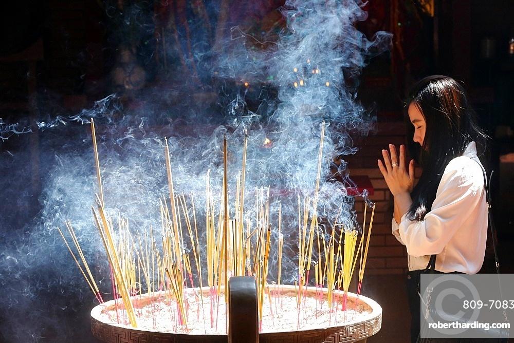 Buddhist worshipper burning incense sticks, Chua On Lang Taoist Temple, Ho Chi Minh City, Vietnam, Indochina, Southeast Asia, Asia