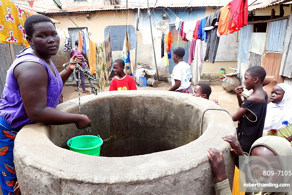 A woman draws water from a well, Lome, Togo, West Africa, Africa
