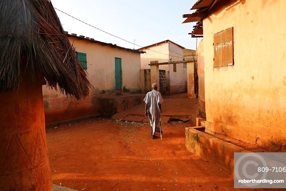 Old man walking in Togoville at sunset, Togoville, Togo, West Africa, Africa