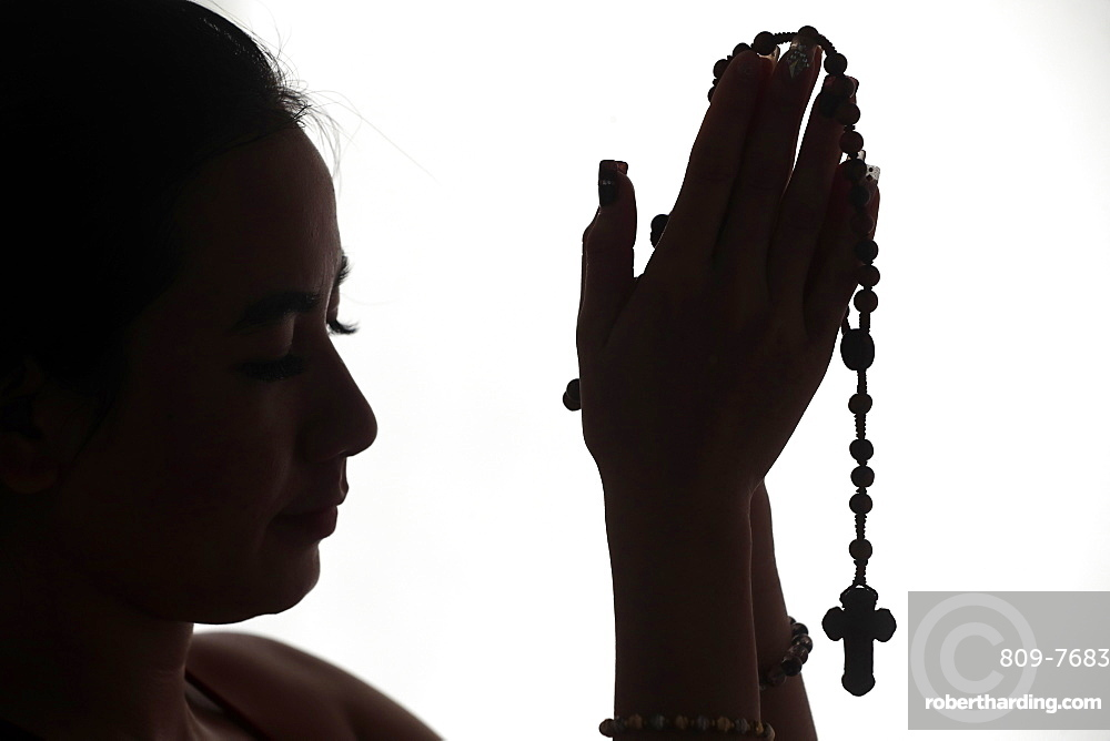 Christian woman praying the Rosary. Vietnam.