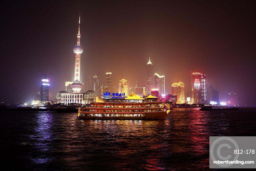 Boat set against Shanghai illuminated skyline, Shanghai, China, Asia