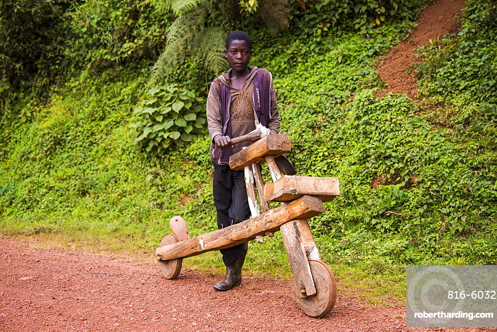 Young boy with his self made bicycle made purely out of wood, southern Uganda, East Africa, Africa