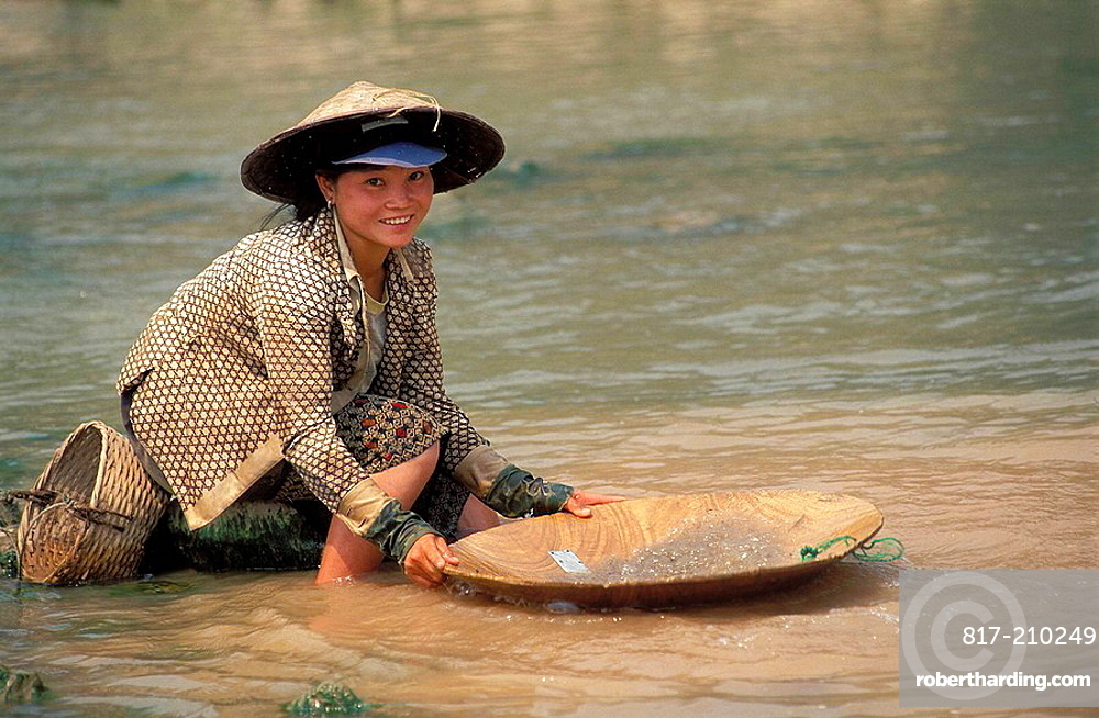 Young woman panning for gold at Mekong river, Laos