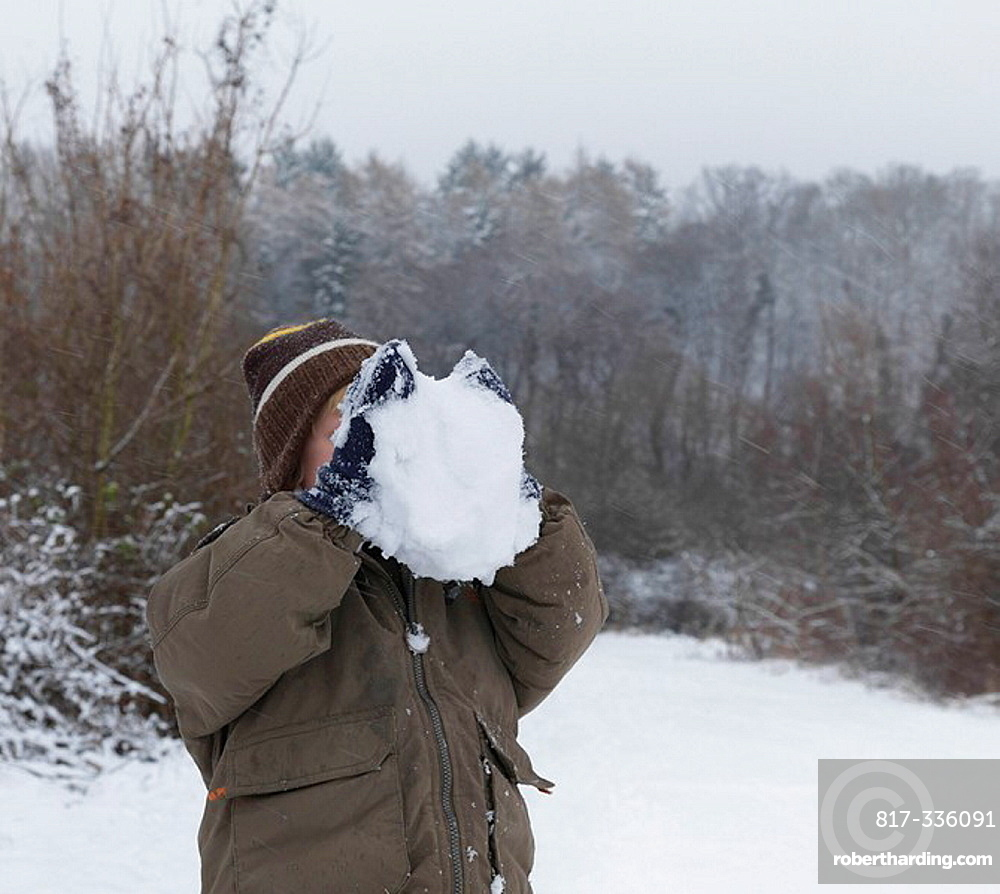 Boy hiding face behind snowball