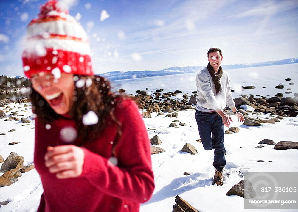 Man throwing snowball at woman