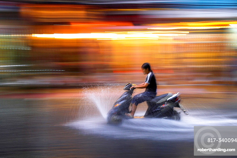 Young woman rides motor scooter at speed in rain along flooded De Tham Street Pham Ngu Lao district Ho Chi Minh City Vietnam