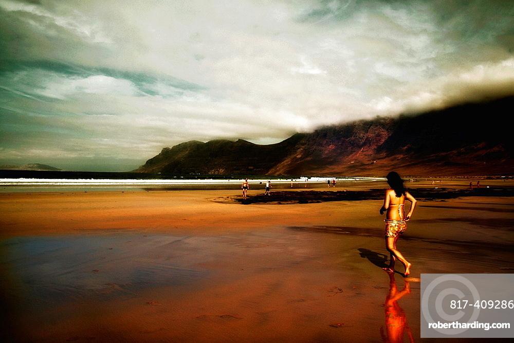 Sunset on Famara beach with girl swimmer Lanzarote