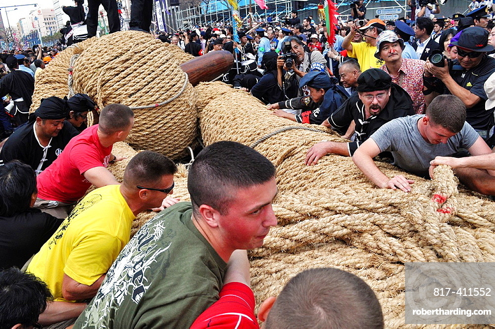 Naha, Okinawa, Japan, American soldiers, local people and tourists pulling the big rope along the Route 58 during the Tug of war Festival, October