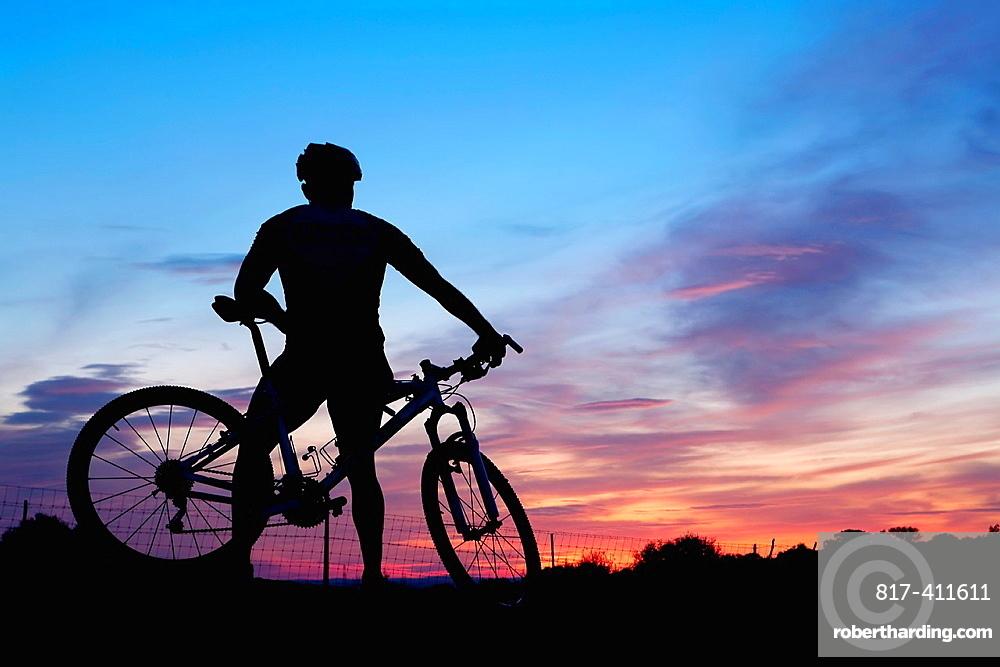 Mountain bike rider resting at dusk