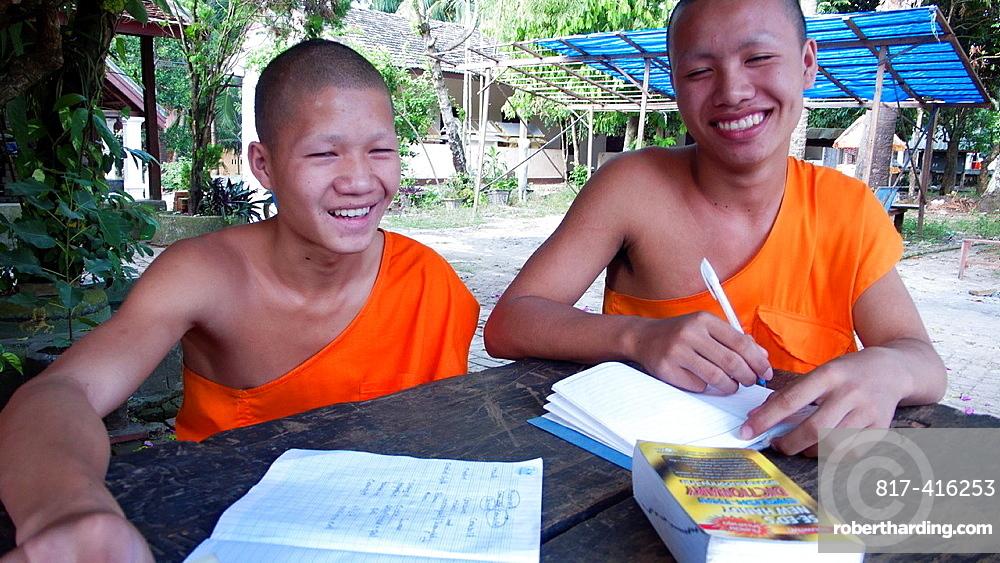 Young monk practises writing temple old quarter Luang Prabang Laos PDR