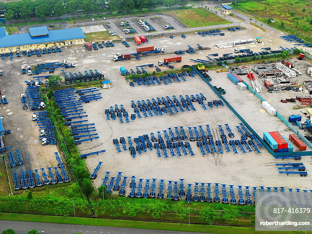 A parking lot full of blue shipping container transport trailers