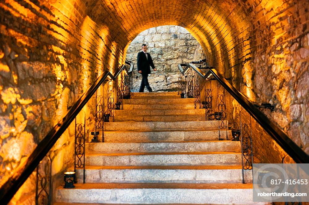 A worker walking down the dark staircase at the hotel Pousada De Sao Tiago in Macau