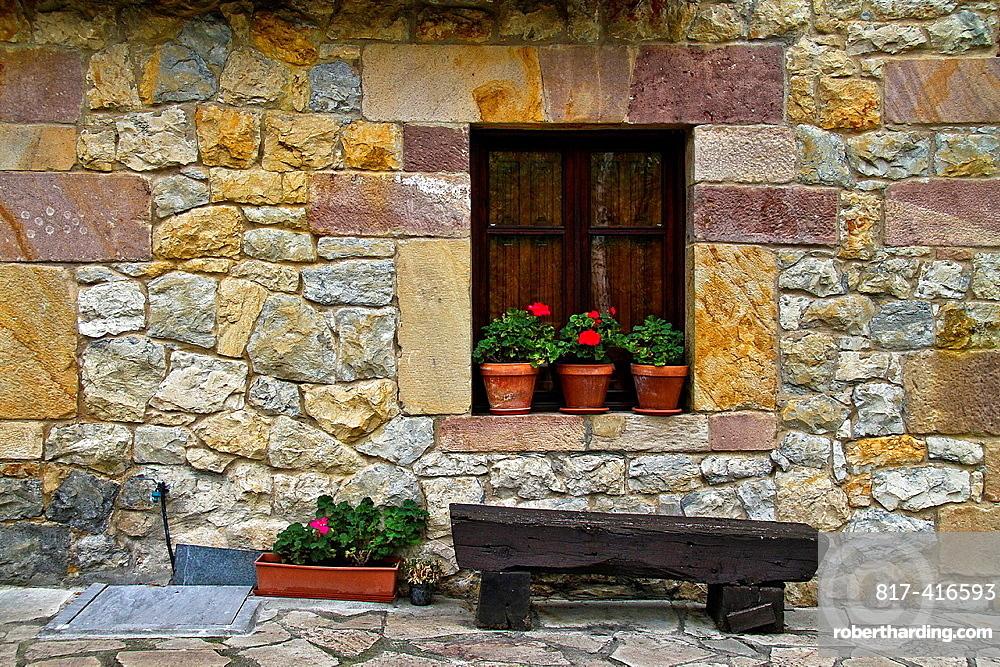 Wood bench outdoors the stone house, Santillana del Mar, Cantabria, Spain