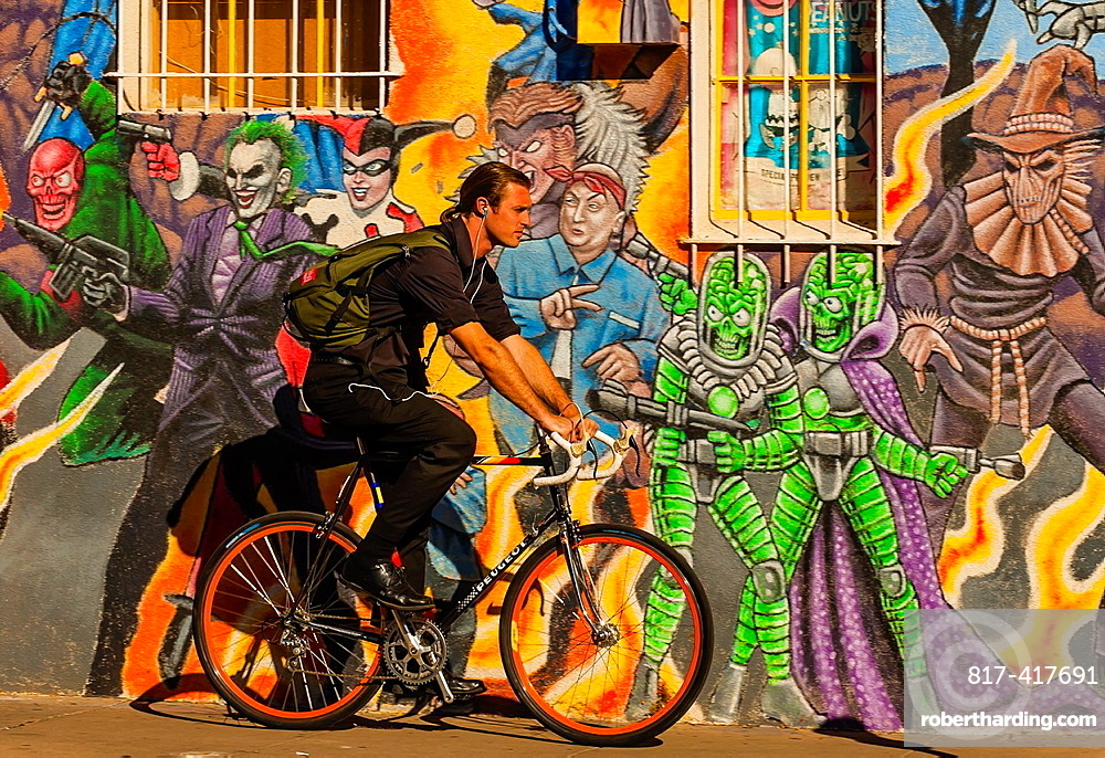 An urban bicyclist riding down the sidewalk with a mural of comic book super heroes on the side of ¥Masks Y Mas¥ store in background, Albuquerque, New Mexico USA