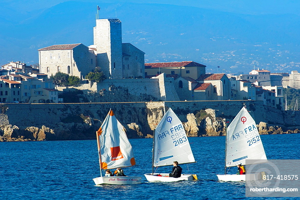 Europe, France, Alpes-Maritimes, Antibes. Boat in front of ramparts on the old city.