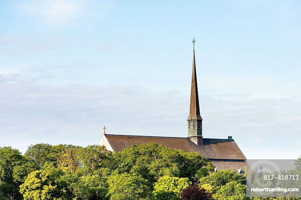 Scandinavian church in natural landscape surrounded by trees at summer
