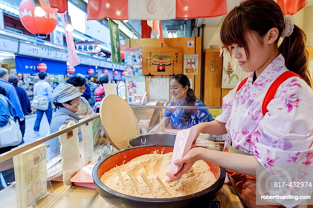 Woman selling sweets in a food stall on the streets of Tokyo, Japan, Asia