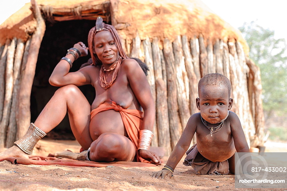 Himba mother and child outside their hut, Epupa falls, Namibia, Africa