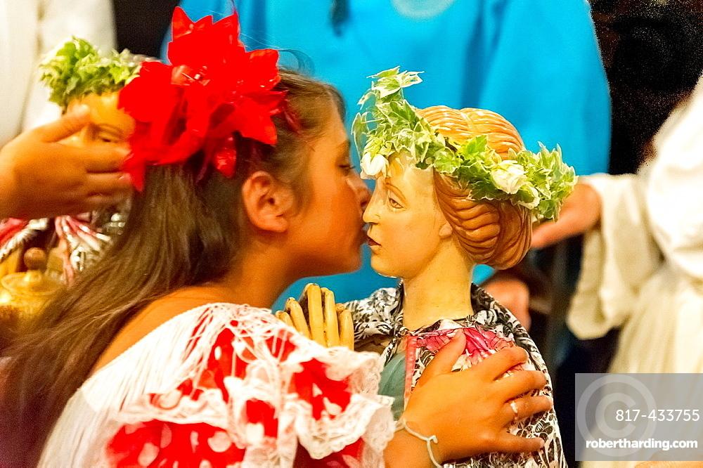 Europe, France, Bouche-du-Rhone, 13, Saintes-Marie-de-la-Mer, pilgrimage of gypsies  Young girl kissing the saints