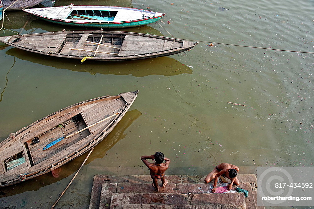 Two young man doing laundry and bathing in the ghats of the river Ganges Varanassi, India