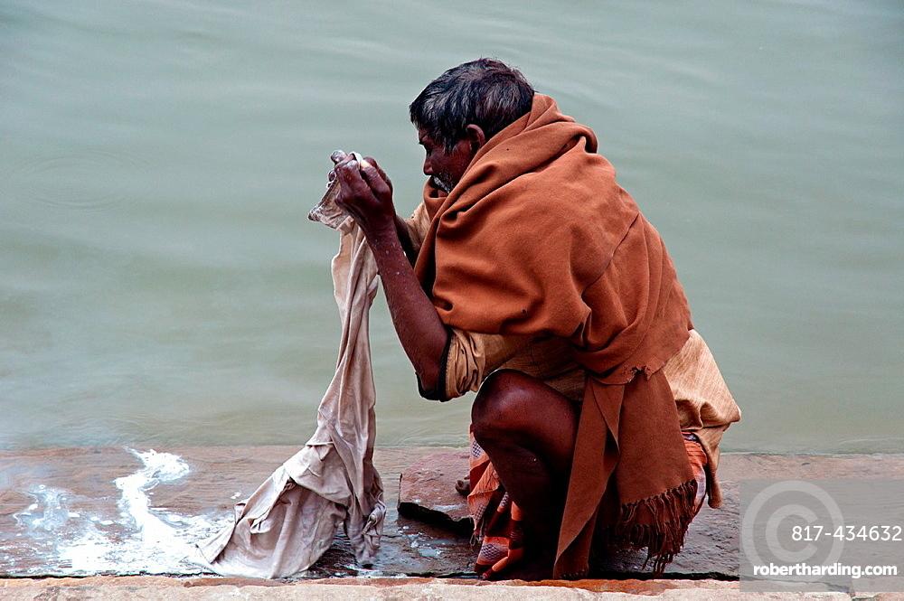 Man washing clothes in the Ganges river Varanasi, Benares, Uttar Pradesh, India
